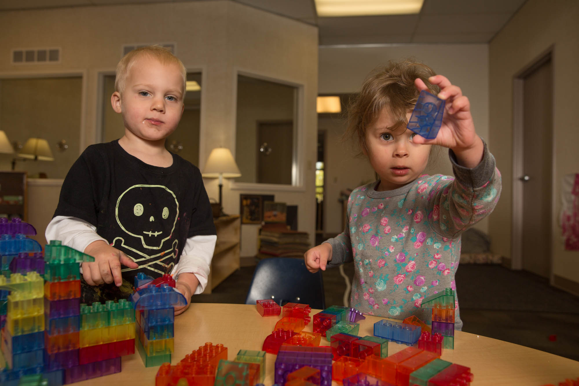 A baby boy and girl playing with blocks
