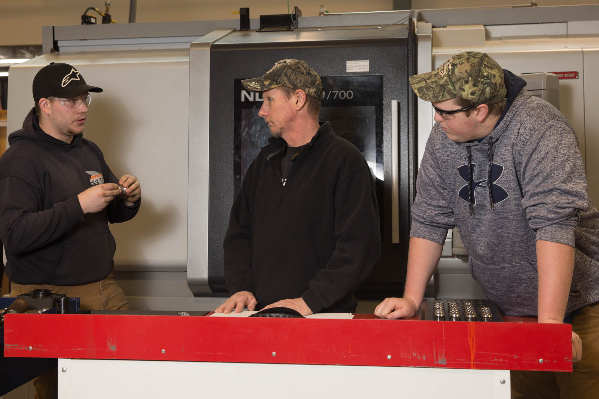 Three men doing CNC machining