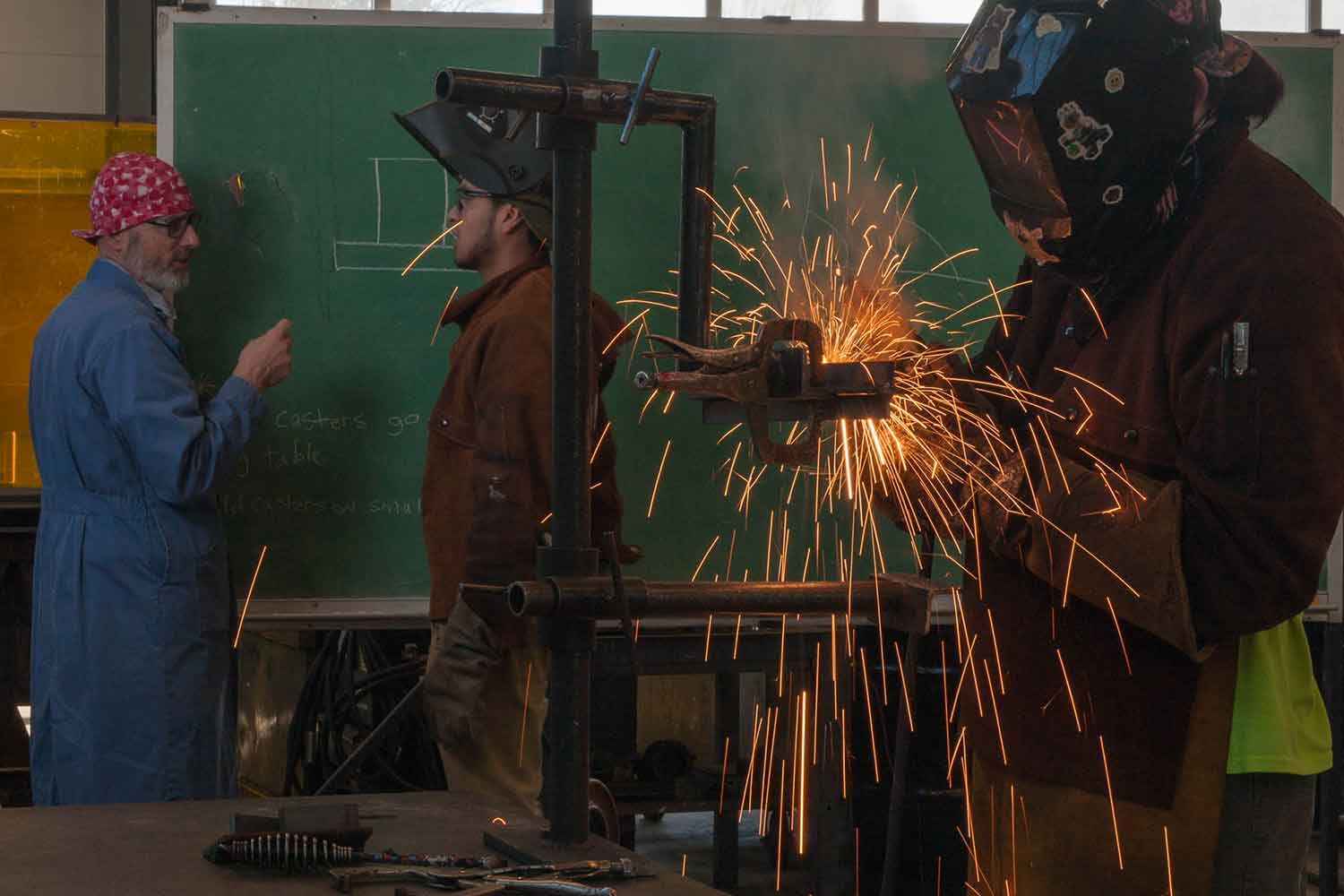 A student welds while an instructor teaches another student in front of a blackboard