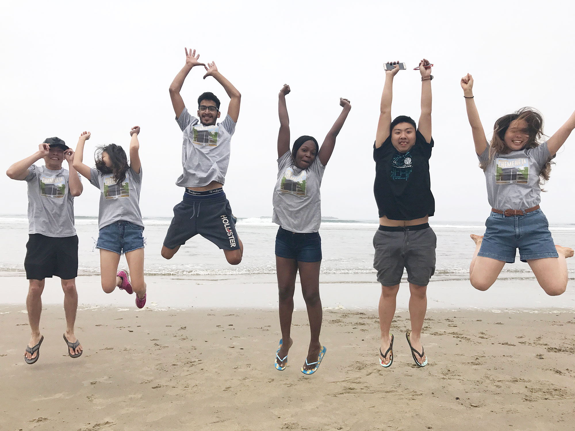 Students jumping in the air at the beach