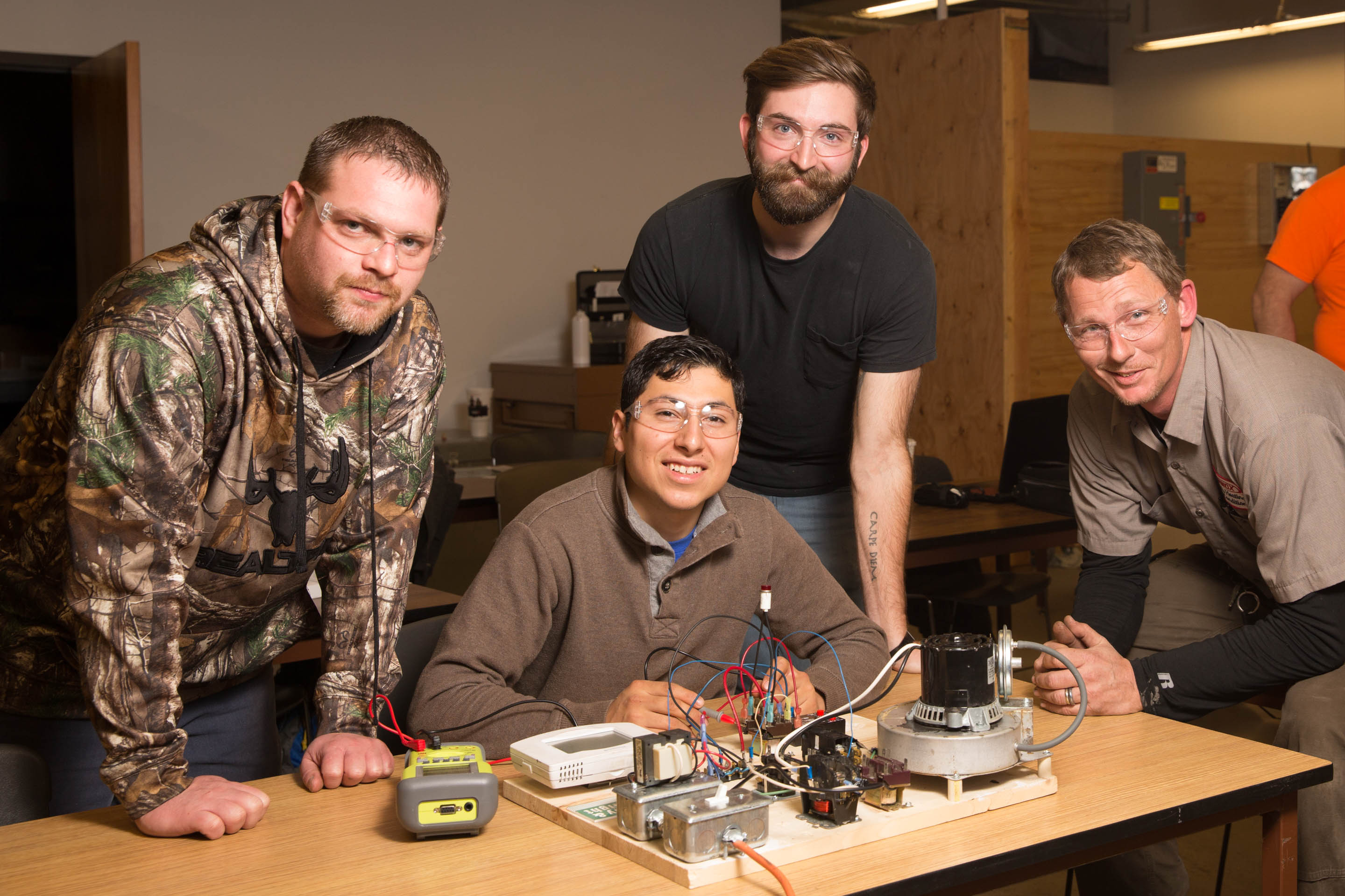 Four men working on electrical systems